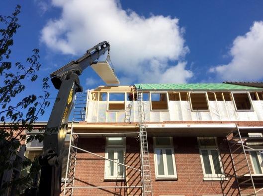 De dakplaten worden het dak opgehesen